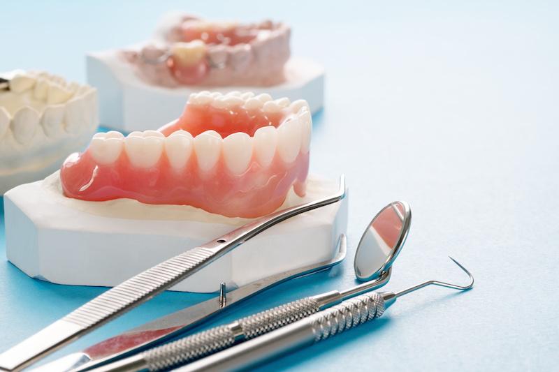Close up , Complete denture or full denture on blue background.