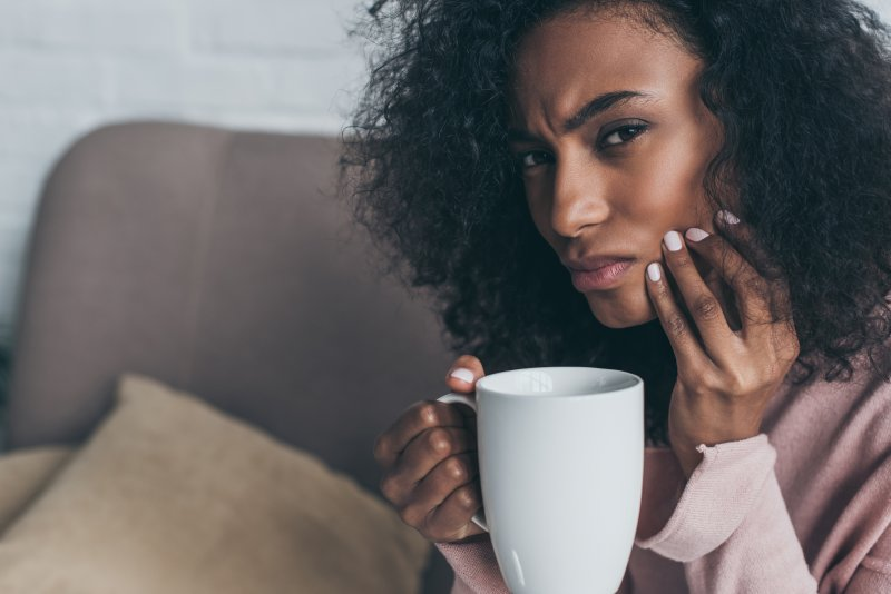 Woman on couch with drink, tooth pain