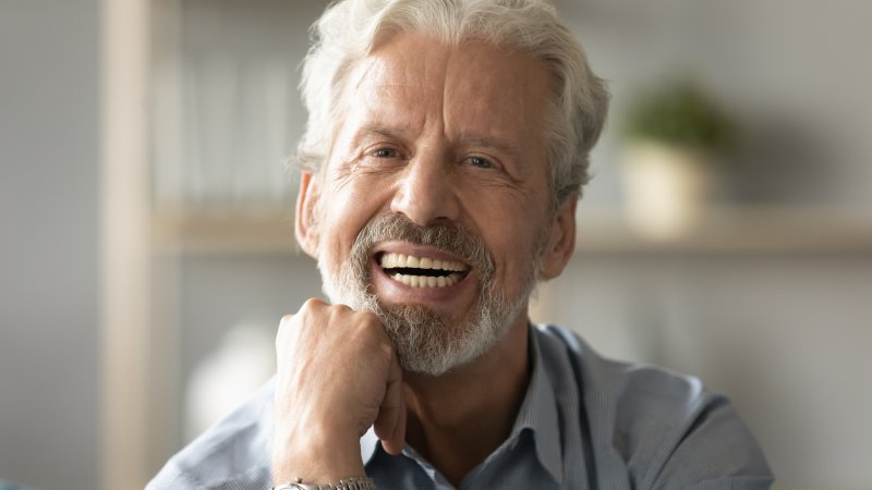 Older man with dentures sitting and smiling